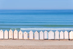 Line of white beach cabins, ocean in the background Stock Photo