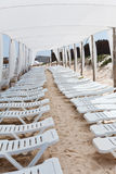 Line from white chaise-longues on beach Stock Image