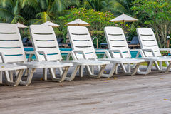 Line of white plastic sunbeds on wooden deck in garden Stock Photos