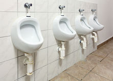 Line of white porcelain urinals in public toilets Stock Photo