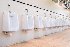 Line of white porcelain urinals public toilets Stock Photos
