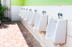 Line of white porcelain urinals in public toilets Royalty Free Stock Images