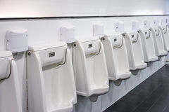 Line of white urinals for men. White urinals for men with electronic flush valve control in public toilet stock image