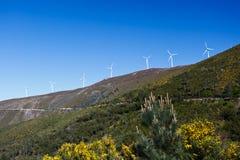 Line of wind driven turbine electricity generators line ridge top in Portugal. Wind mill turbine electricity generators lining ridge top above road to Coimbra stock image