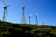 Line of windmills for renewable electric energy production Royalty Free Stock Photo