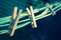 On the line. Wooden clothes pegs attached to a washing line Stock Images