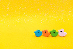 A line of wooden toy ducks on bright glittery yellow background Royalty Free Stock Image