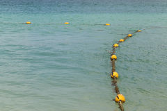 Line of yellow buoys on the rope floating in the sea Stock Photo