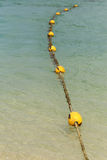 Line of yellow buoys on the rope floating in the sea Stock Photos