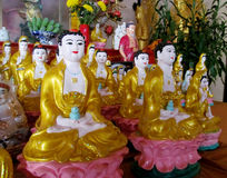 Line of yellow-dressed buddha statues Stock Photos