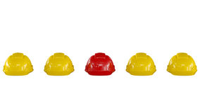 Line of yellow safety helmets with a red one Royalty Free Stock Images