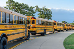 Line of yellow school buses - back to school. Buses in a single file line along sidewalk outside high school in afternoon Royalty Free Stock Images
