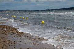 Line of yellow warning buoys on pebble beach. Stock Photography