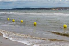Line of yellow warning buoys on pebble beach. Stock Photo
