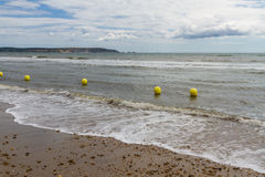 Line of yellow warning buoys on pebble beach. Royalty Free Stock Images