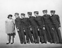 Line of young bellhops smiling at girl Stock Image