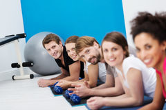 Line of young friends exercising in the gym Stock Photo