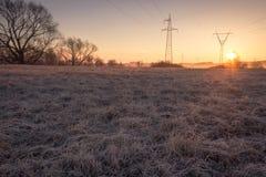 Linea ad alta tensione supporti in nebbia alla mattina gelida di alba della molla Fotografia Stock