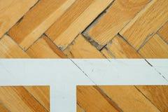 Linea bianca in corridoio Il pavimento di legno consumato della palestra con la marcatura variopinta allinea Immagini Stock