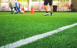 Linea bianca del campo di formazione di calcio con il bambino nel fondo Fotografia Stock
