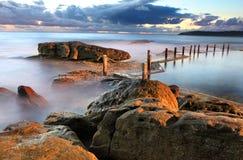 Linea costiera di alba e stagno della roccia di Mahon immagini stock