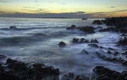 Linea costiera di tramonto con le rocce e l'attività al suolo fotografia stock libera da diritti