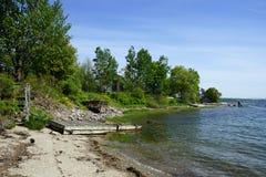 Linea costiera rocciosa con il pilastro nella distanza ed in alberi verdi Immagine Stock