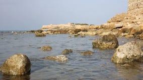 Linea costiera rocciosa di un mare blu con la fortezza antica di Rethymno sui precedenti unfocused stock footage