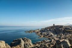 Linea costiera rocciosa e torre genovese a Punta Spano in Corsica Immagini Stock