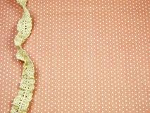 Linea del pizzo sul fondo arancio del pois fotografia stock