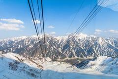 Linea della cabina di funivia che va all'itinerario alpino di Tateyama Kurobe sulla neve Immagine Stock Libera da Diritti