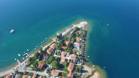 Linea della costa della penisola del sobborgo del Montenegro con le costruzioni ed i cottage Metraggio di vista superiore archivi video