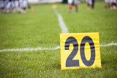 Linea delle yard di calcio con un segno nella priorità alta Fotografie Stock Libere da Diritti