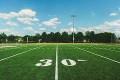 Linea delle yard 30 sul campo e sul cielo blu di football americano immagini stock