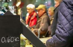 Linea di attesa ad un forno dietro un bordo di prezzi con la gente deliberatamente vaga fotografia stock