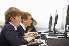 Linea di bambini nella classe del computer della scuola Immagini Stock