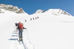 Linea di gente che sale una montagna sui cieli Immagini Stock