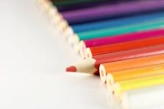 Linea di matite variopinte con un individuo Fotografia Stock