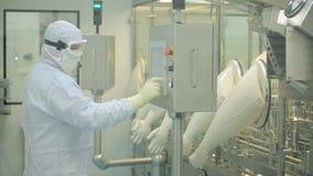 Linea di produzione farmaceutica lavoratore sul lavoro Ampolle di sollevamento del braccio robot alla catena di imballaggio in fa fotografia stock libera da diritti