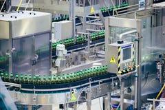 Linea di produzione imbottigliante automatizzata della birra Bottiglie di birra imballate sul nastro trasportatore immagini stock libere da diritti
