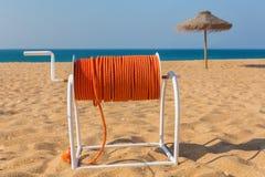Linea di sicurezza sulla spiaggia con il parasole ed il mare Fotografia Stock