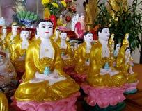 Linea di statue giallo-vestite di Buddha Fotografie Stock