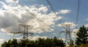 Linea di trasmissione ad alta tensione di energia elettrica torre del pilone su cielo blu e sul fondo bianco della nuvola Fotografia Stock