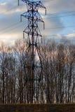 Linea di trasmissione ad alta tensione in primavera foresta al tramonto contro lo sfondo del cielo blu di aprile con le nuvole le Immagini Stock Libere da Diritti