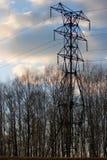 Linea di trasmissione ad alta tensione in primavera foresta al tramonto contro lo sfondo del cielo blu di aprile con le nuvole le Immagini Stock