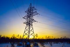 Linea di trasmissione di elettricità nell'inverno al tramonto Immagine Stock