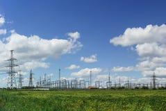 Linea di trasmissione e sottostazione elettrica sui precedenti di cielo blu Fotografia Stock Libera da Diritti
