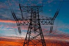 Linea di trasmissione su un fondo di bello tramonto con le tonalità di rosso e di luci gialle Fotografia Stock Libera da Diritti