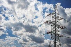 Linea elettrica ad alta tensione contro lo sfondo delle nuvole e del cielo blu Concetto di ingegneria energetica e di elettricità Fotografia Stock