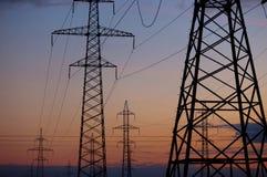 Linea elettrica ad alta tensione del cuscinetto del metallo al tramonto Immagine Stock